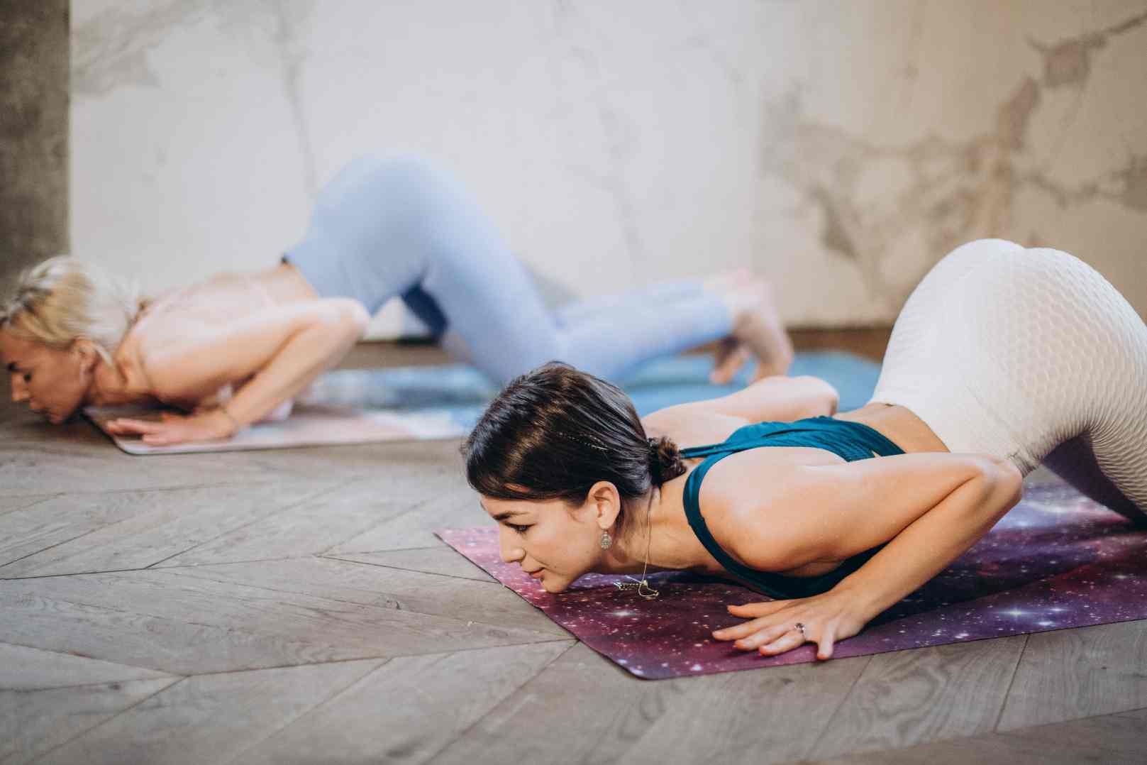 Two Young Women practice the Caterpillar Pose