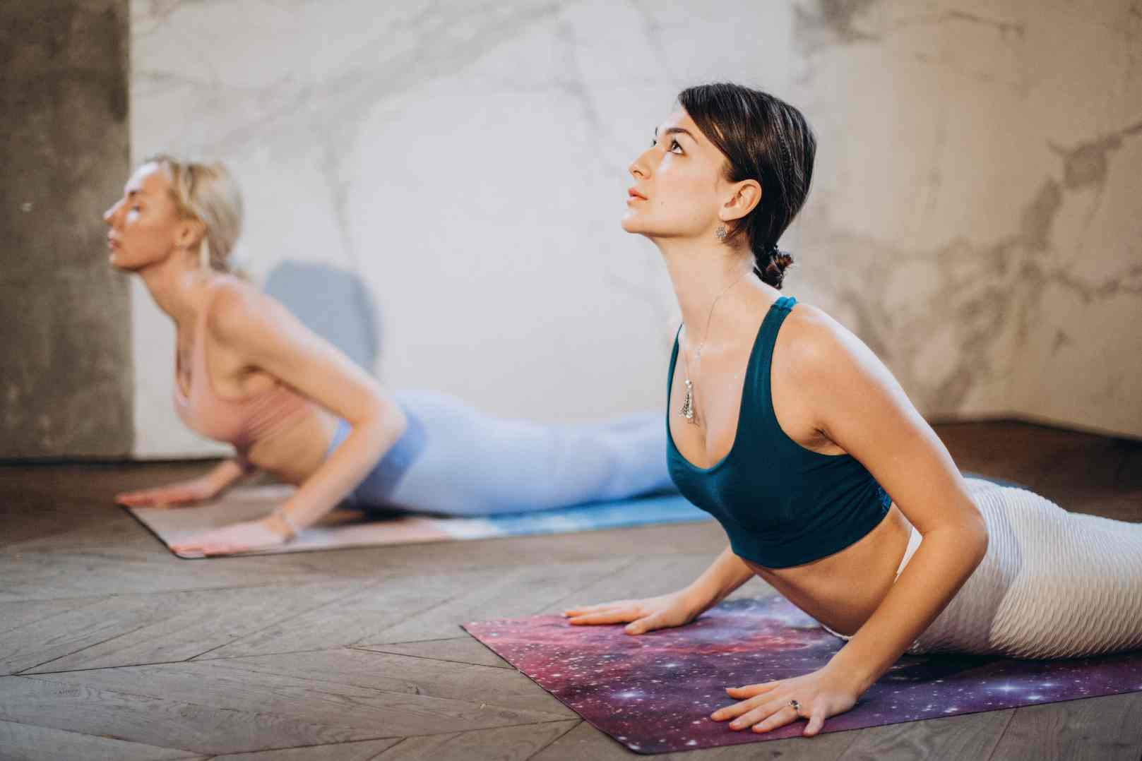 Two Young Women practice the Cobra Pose