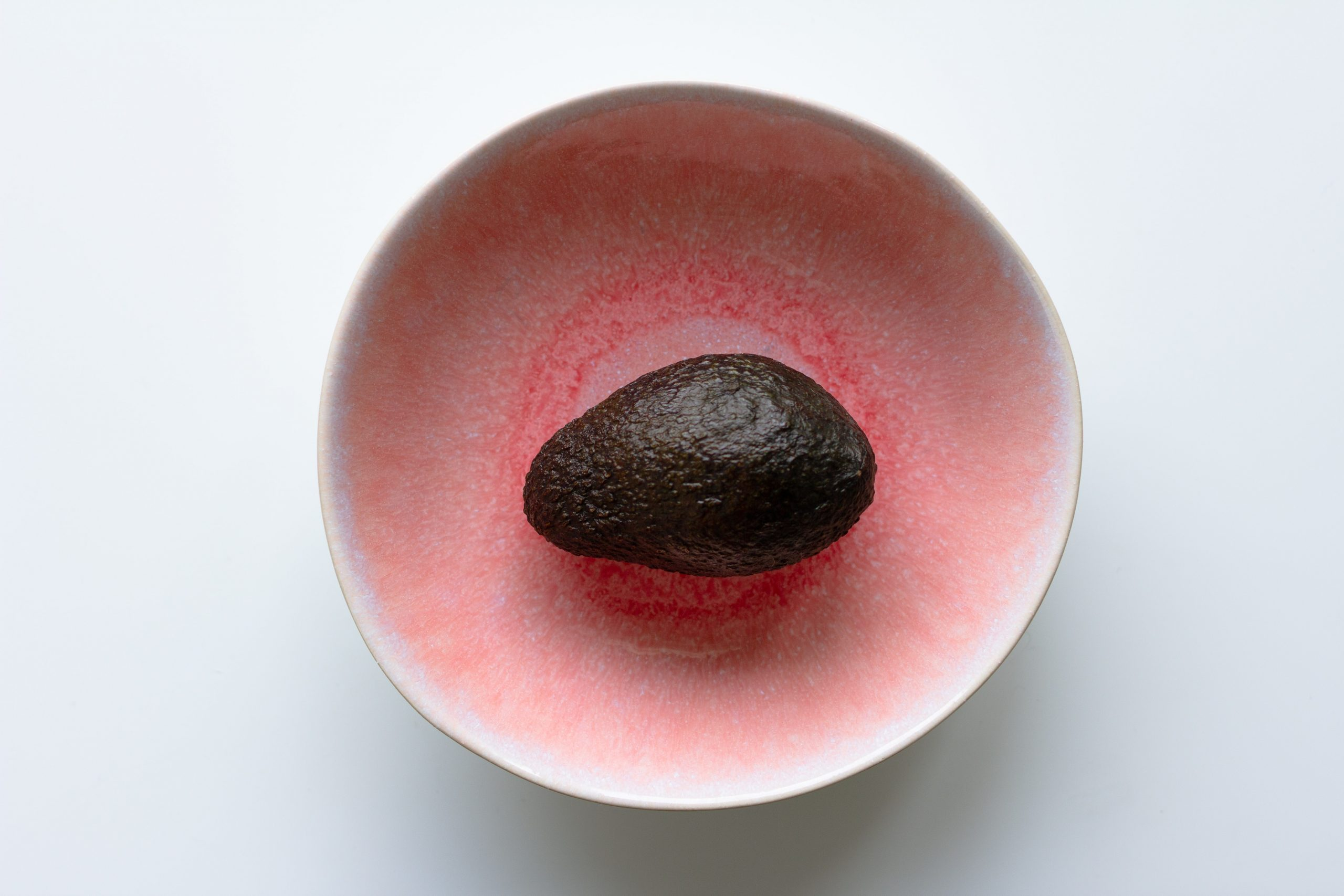 Avocado in a pink rustic bowl